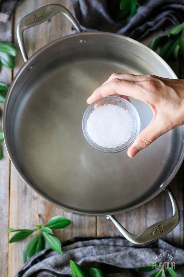 adding salt to pot of boiling water