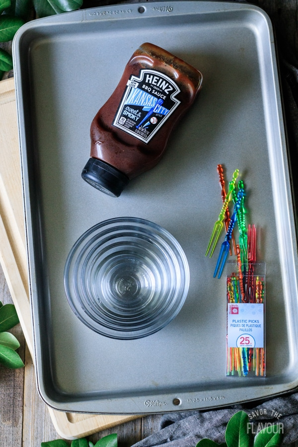 barbecue sauce, cookie sheet, cutting board, glass bowls, and plastic picks