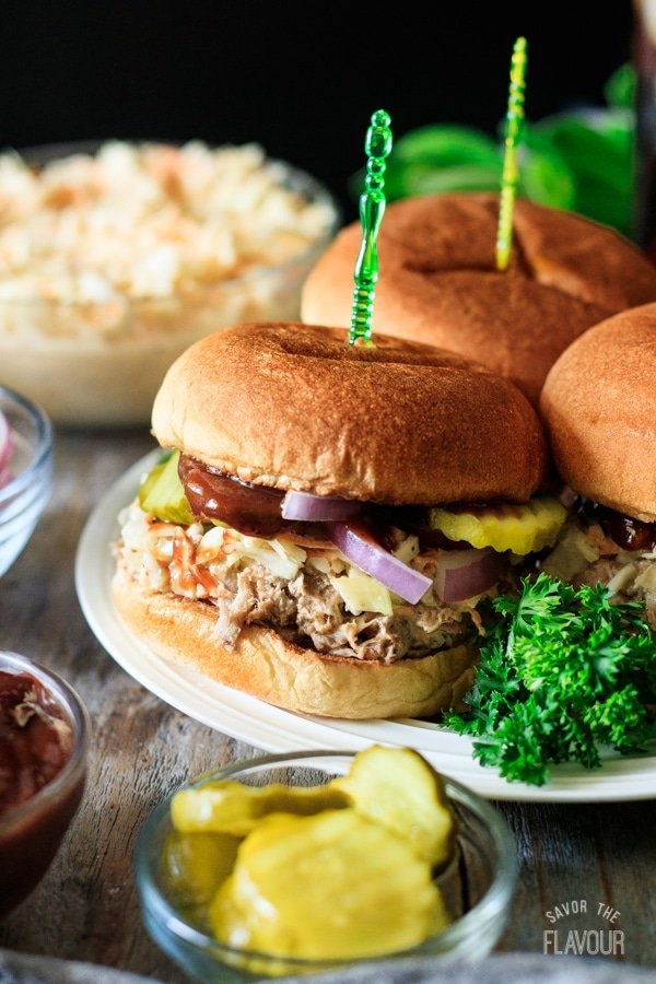 pulled pork sandwich on a plate with pickles