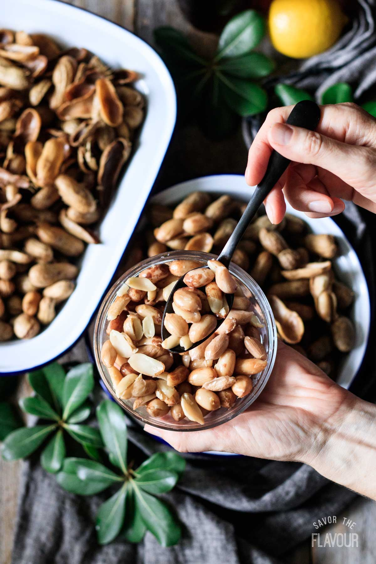 person holding a bowl and spoon of shelled boiled peanuts