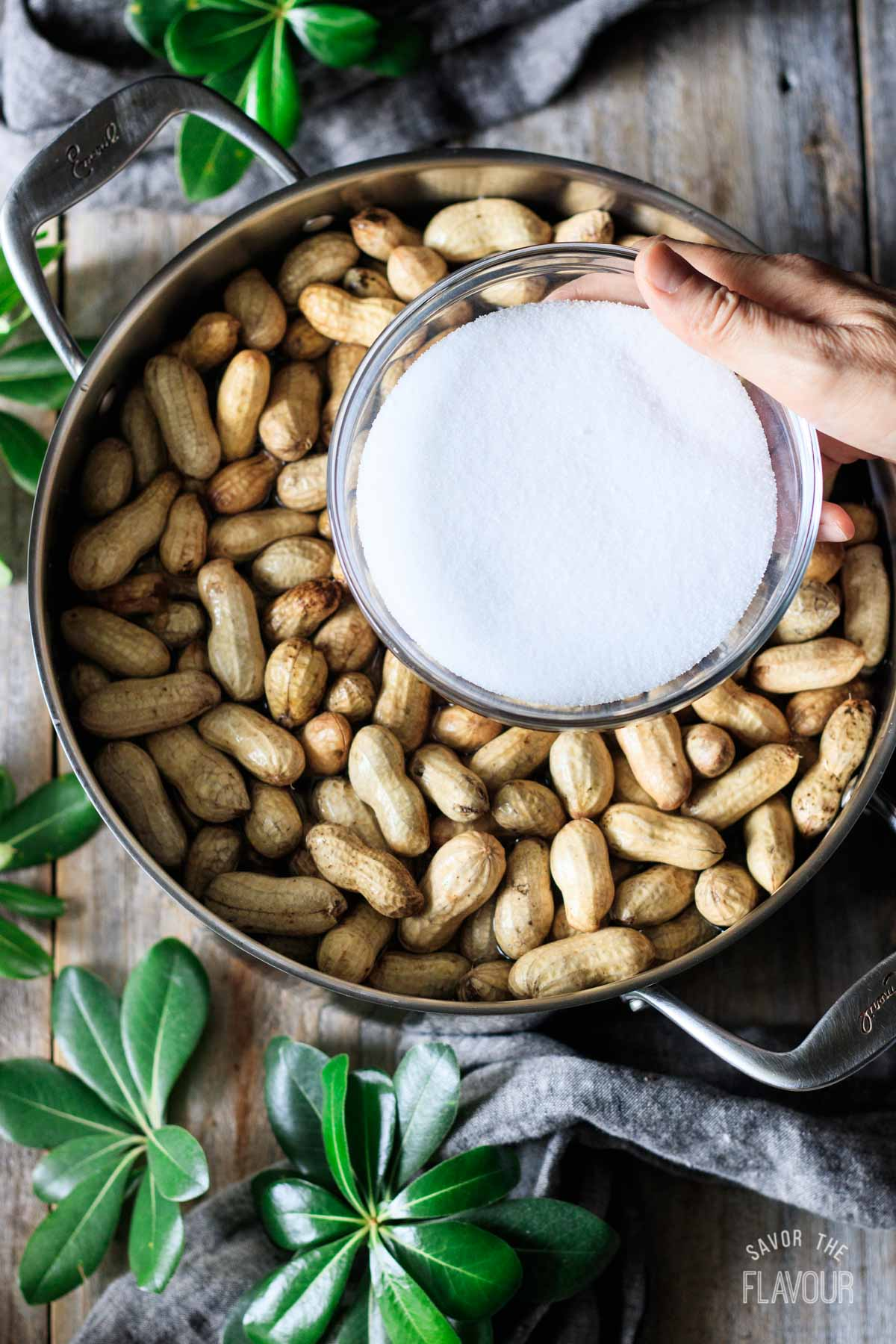 adding salt to a pot of boiled peanuts