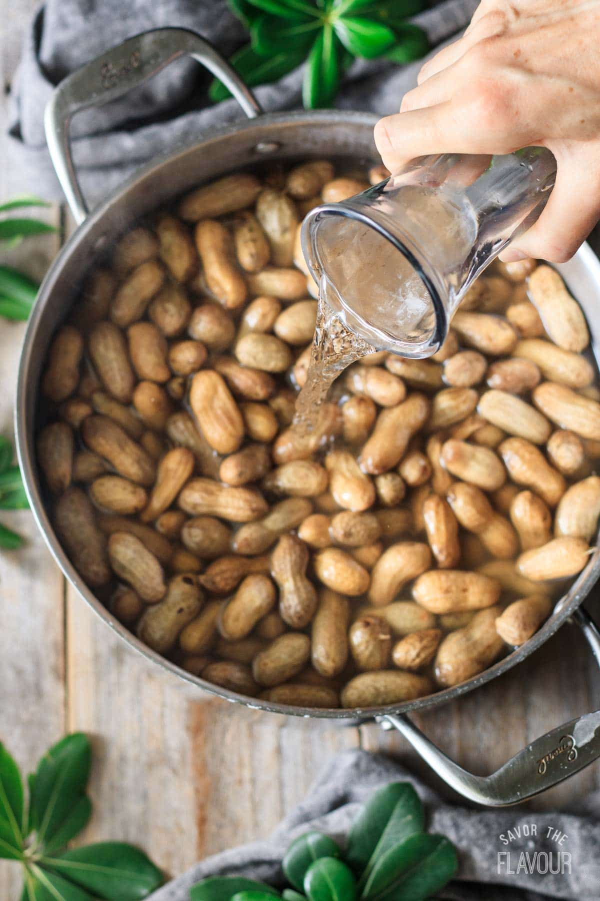 pouring water into a pot of boiled peanuts