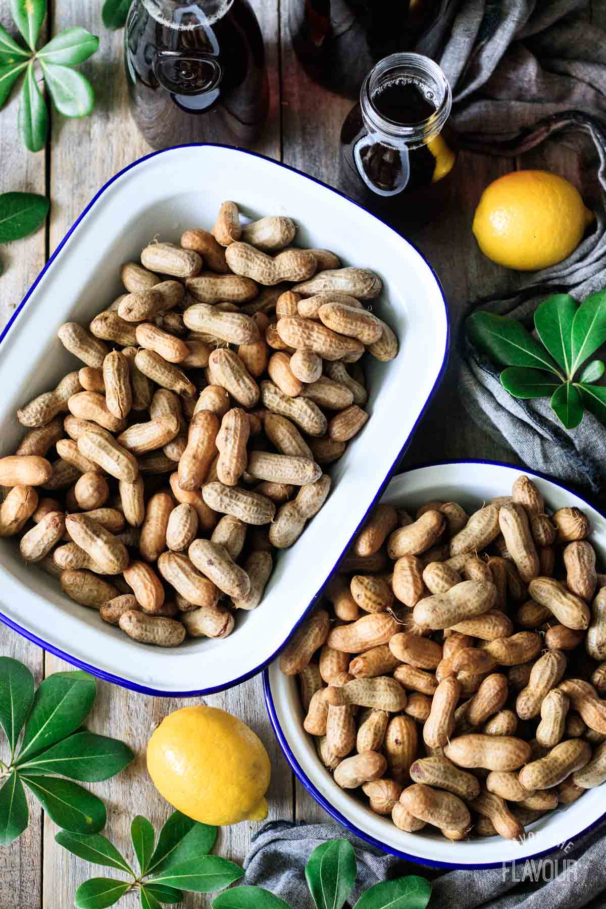 two dishes of boiled peanuts with bottles of sweet tea