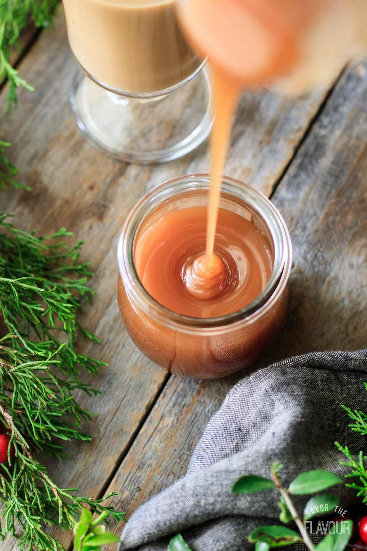 pouring caramel sauce into a jar
