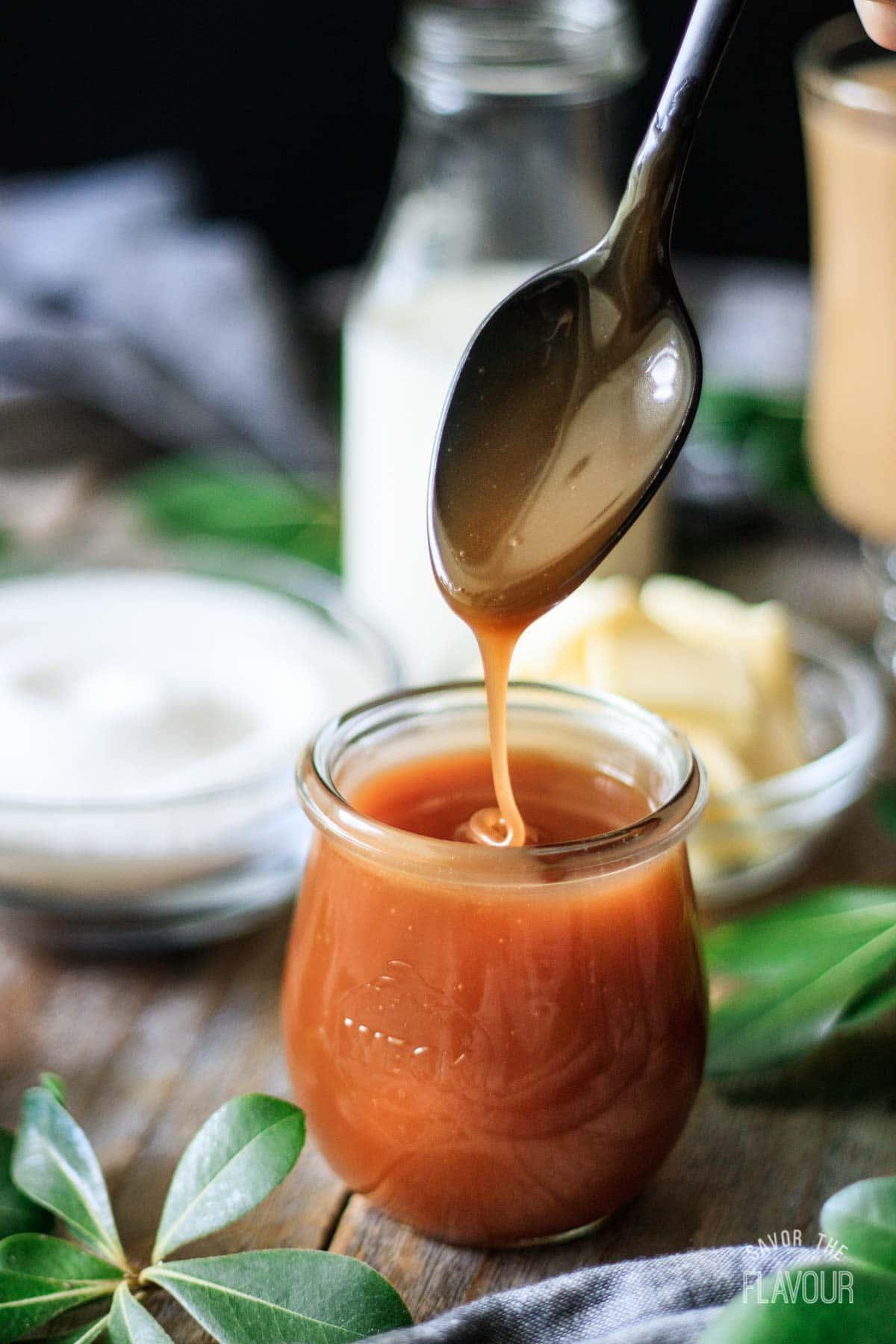 person dipping a spoon into homemade caramel sauce