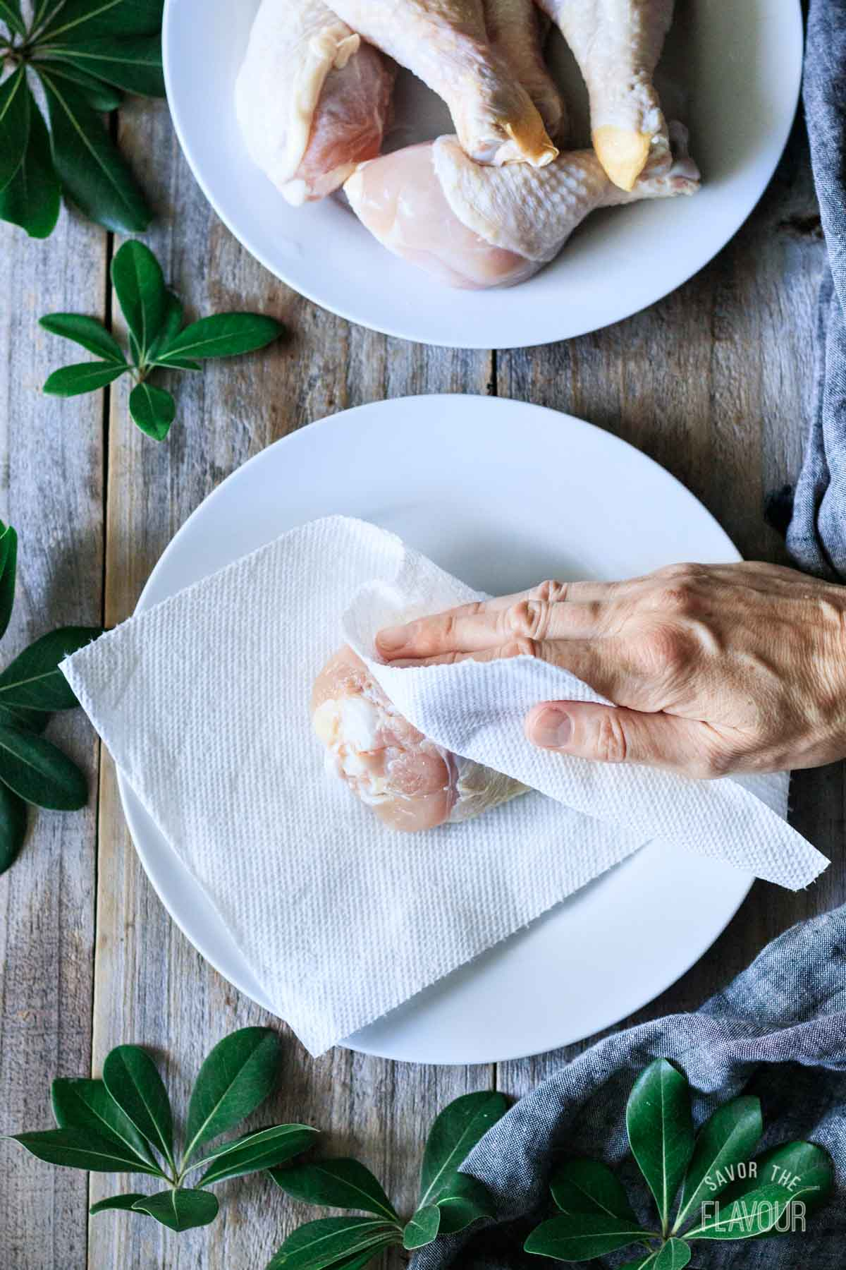 patting dry raw chicken with paper towel