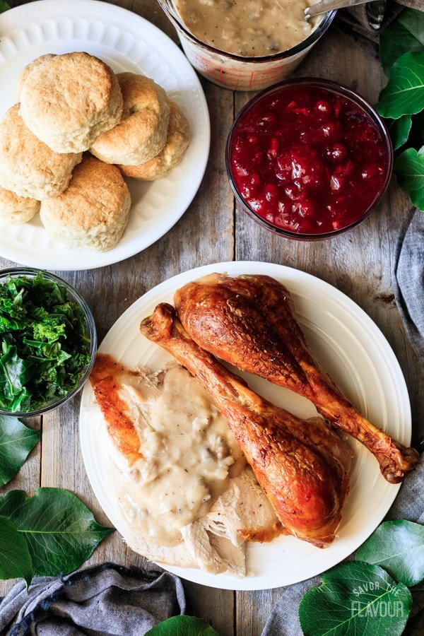 plate of turkey and giblet gravy with biscuits, kale, and cranberry sauce