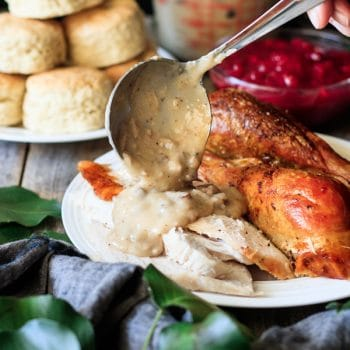 pouring giblet gravy on slices of roasted turkey