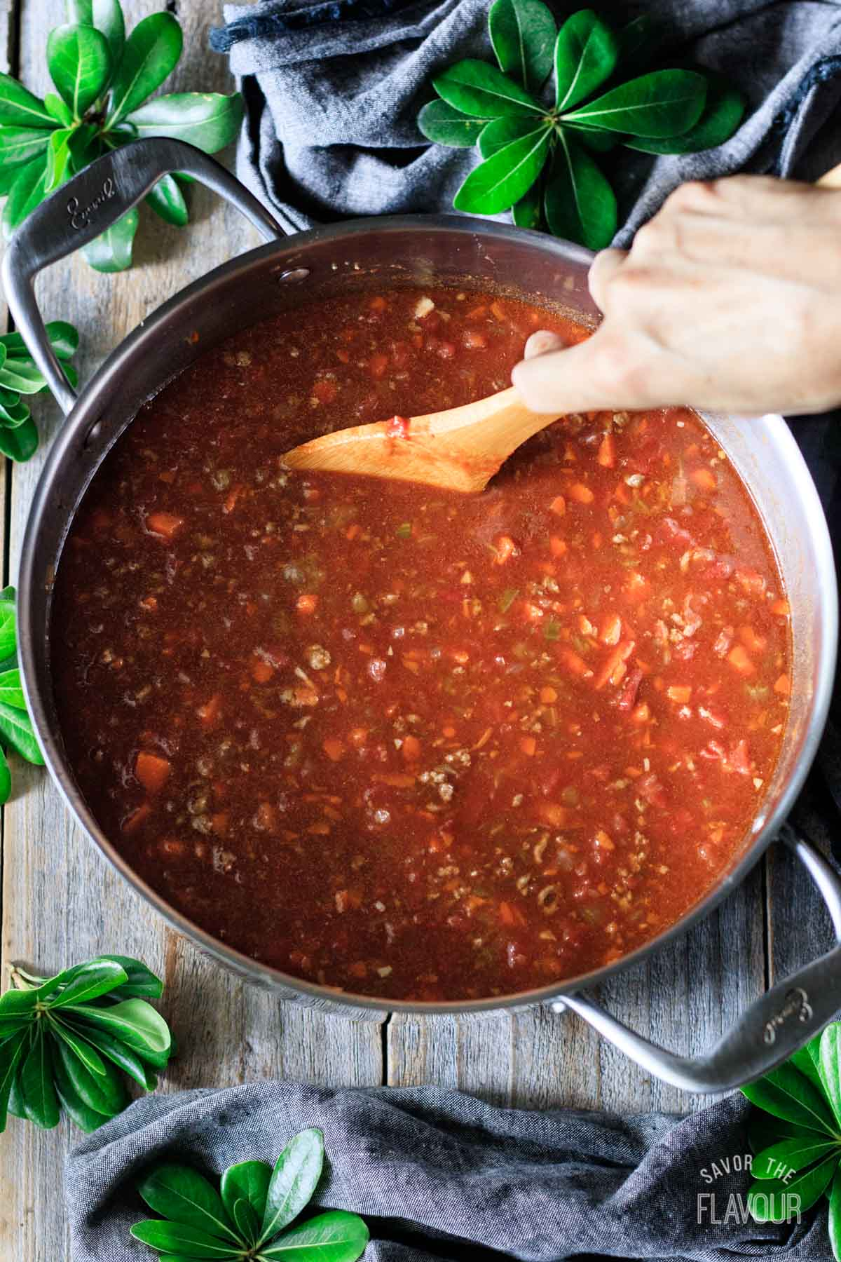 stirring hamburger barley soup with a wooden spoon