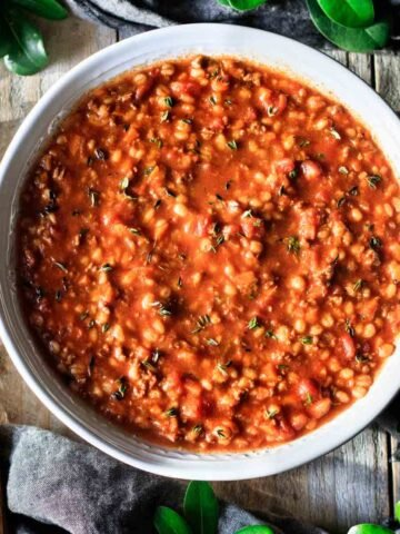 bowl of hamburger barley soup with a wooden spoon