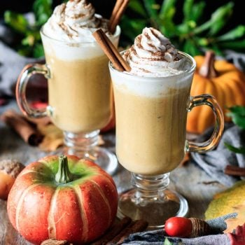 two glasses of pumpkin spice latte with a pumpkin