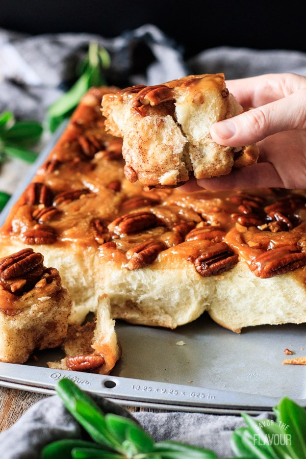 person holding a piece of maple pecan sticky bun