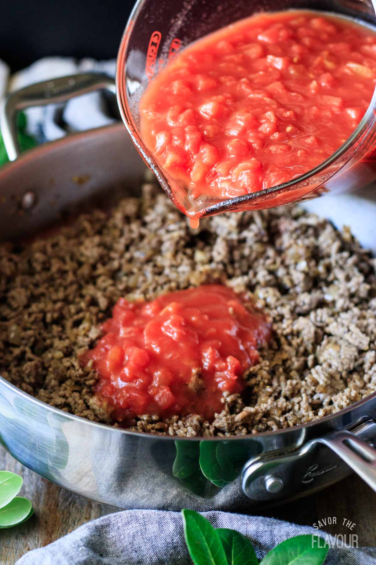 pouring tomatoes into a pan of hamburger meat