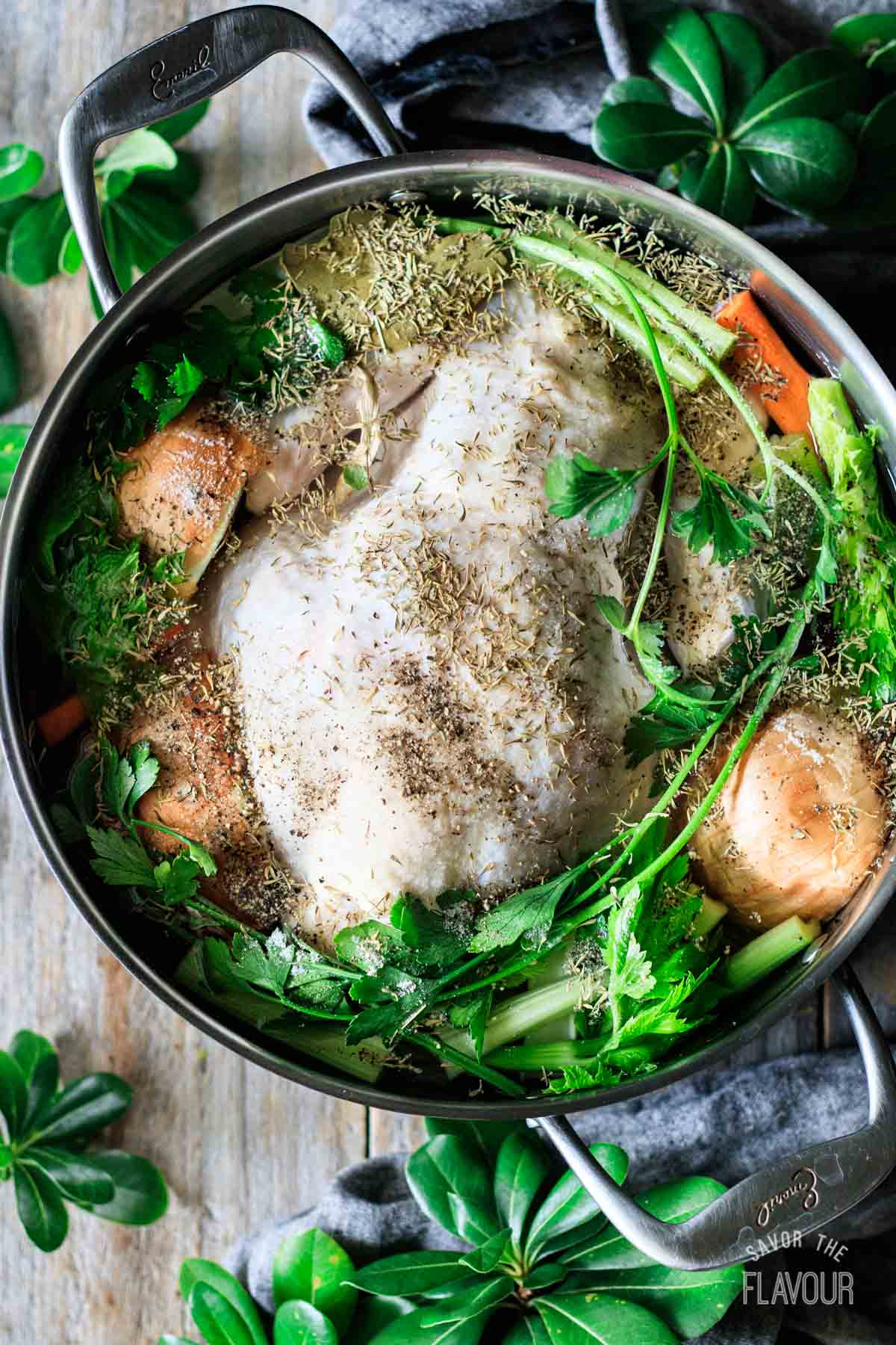 raw chicken in a pot of water with spices and veggies