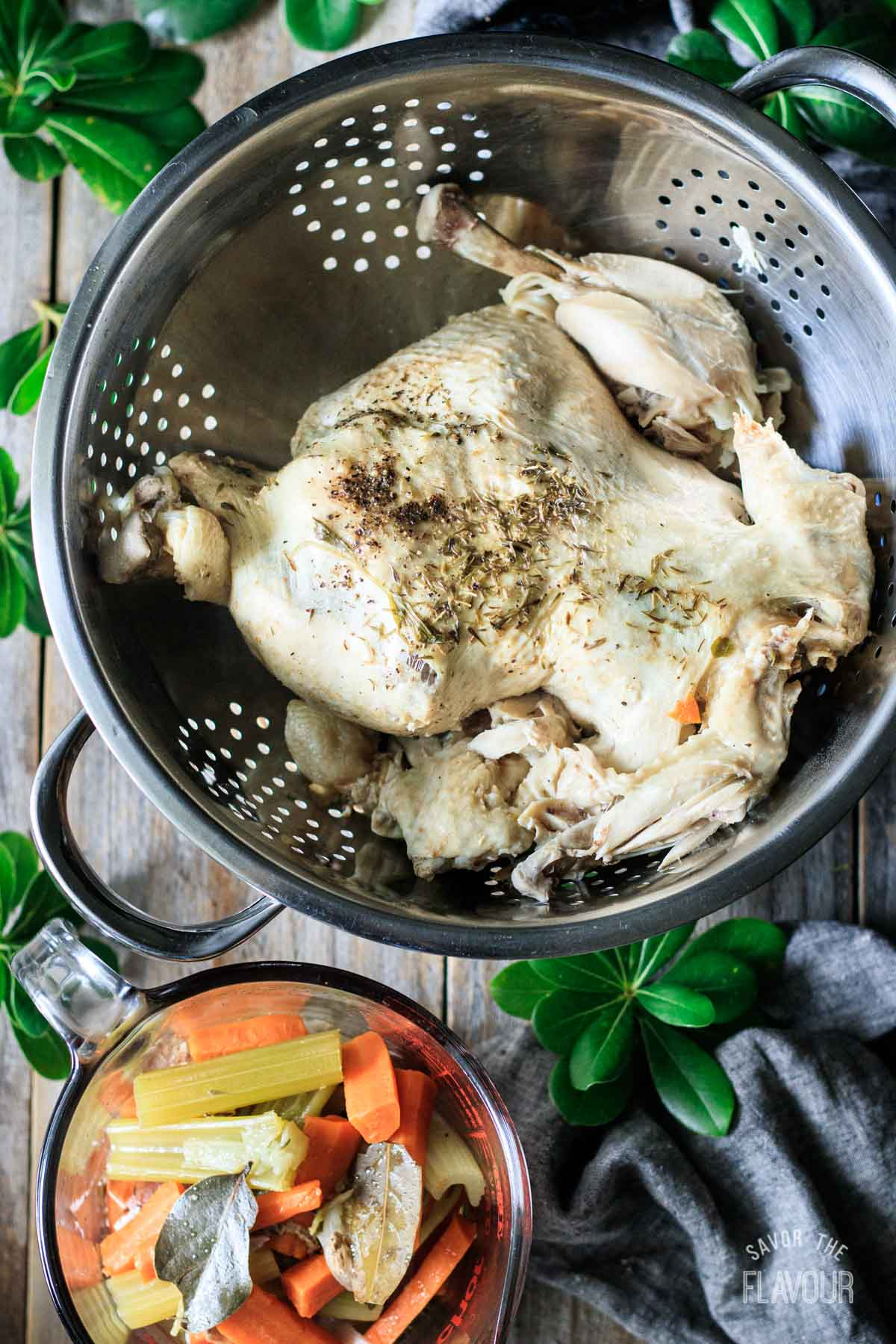 straining the boiled chicken in a colander