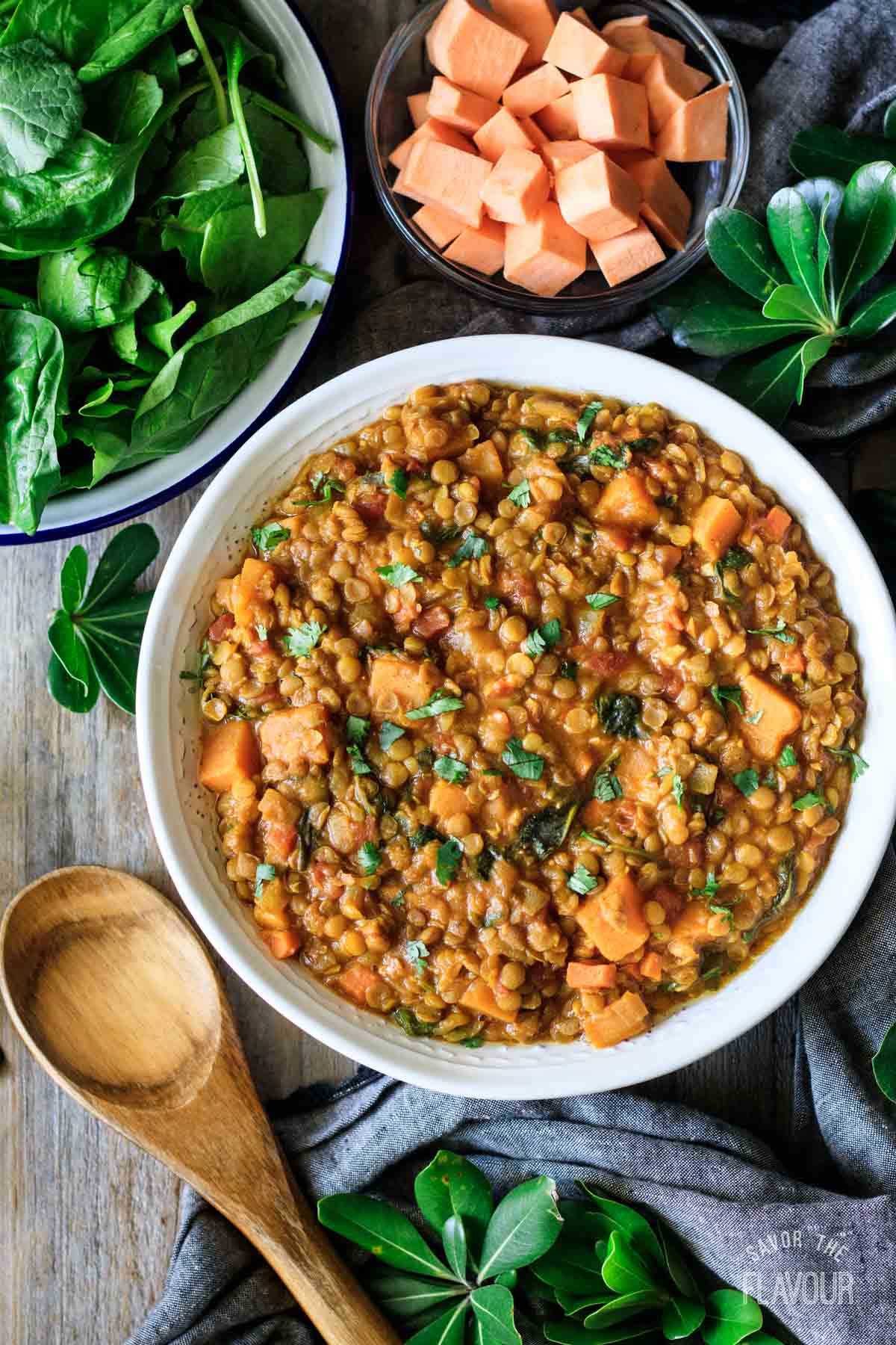 bowl of Moroccan lentil stew with a bowl of spinach