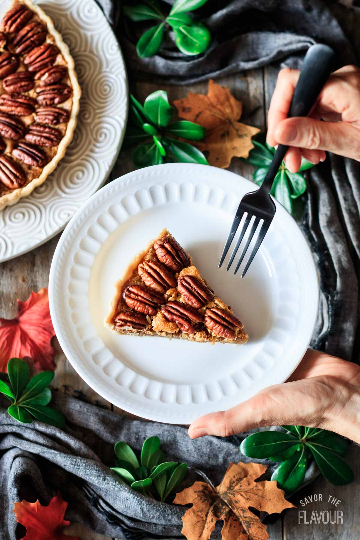 person holding a slice of pecan pie with a fork