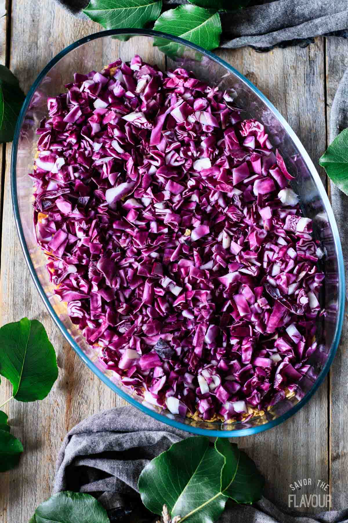 adding shredded red cabbage to casserole dish