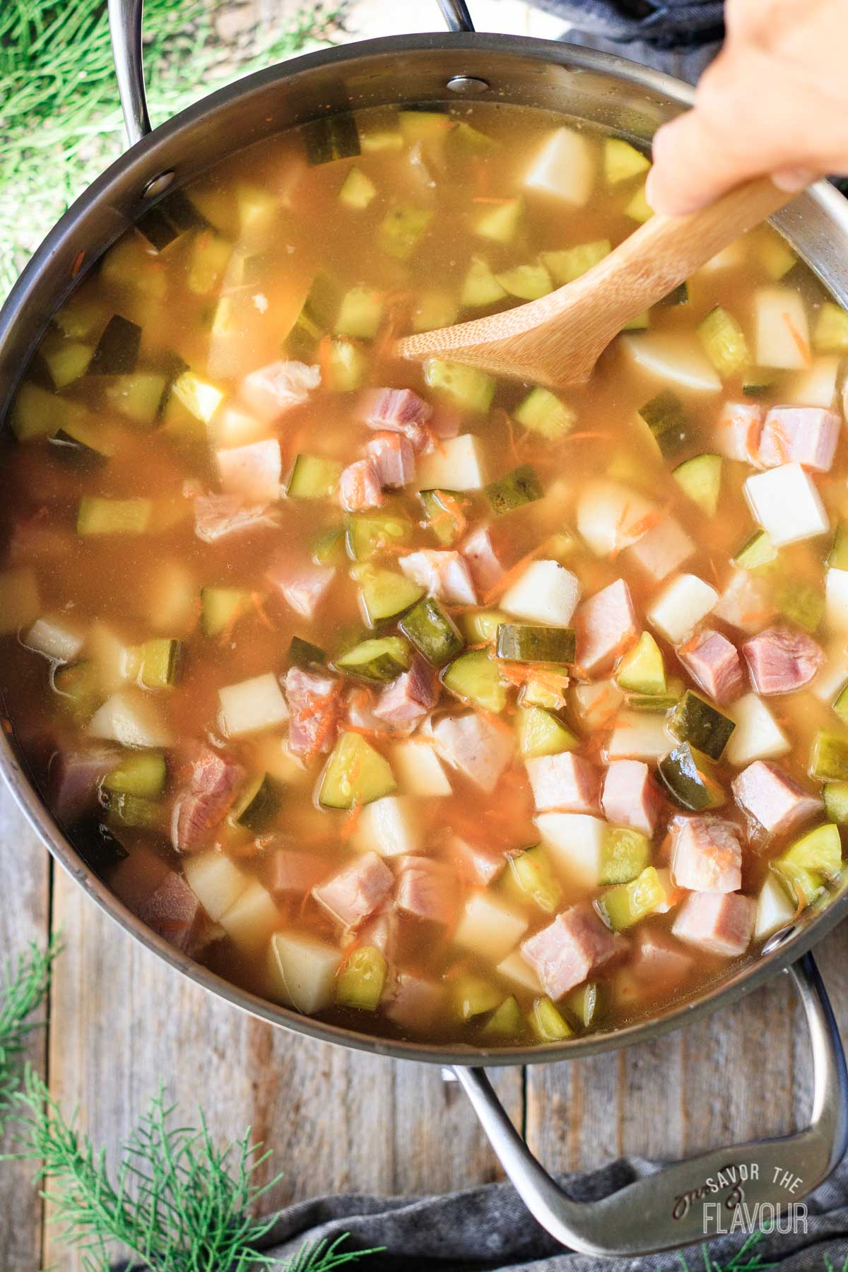 stirring a pot of broth with pickles, ham, and potatoes
