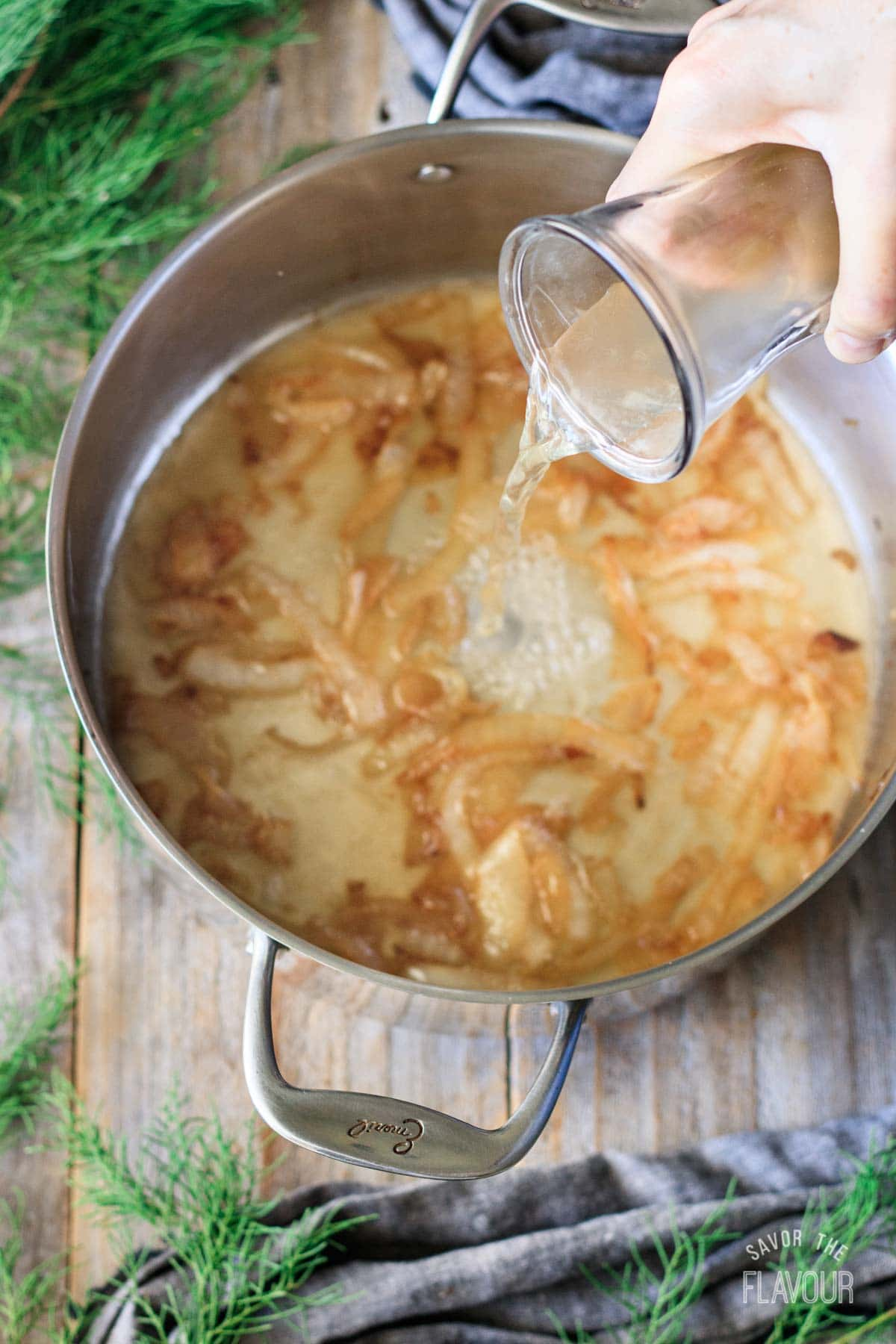 pouring chicken broth into a pot of cooked onions