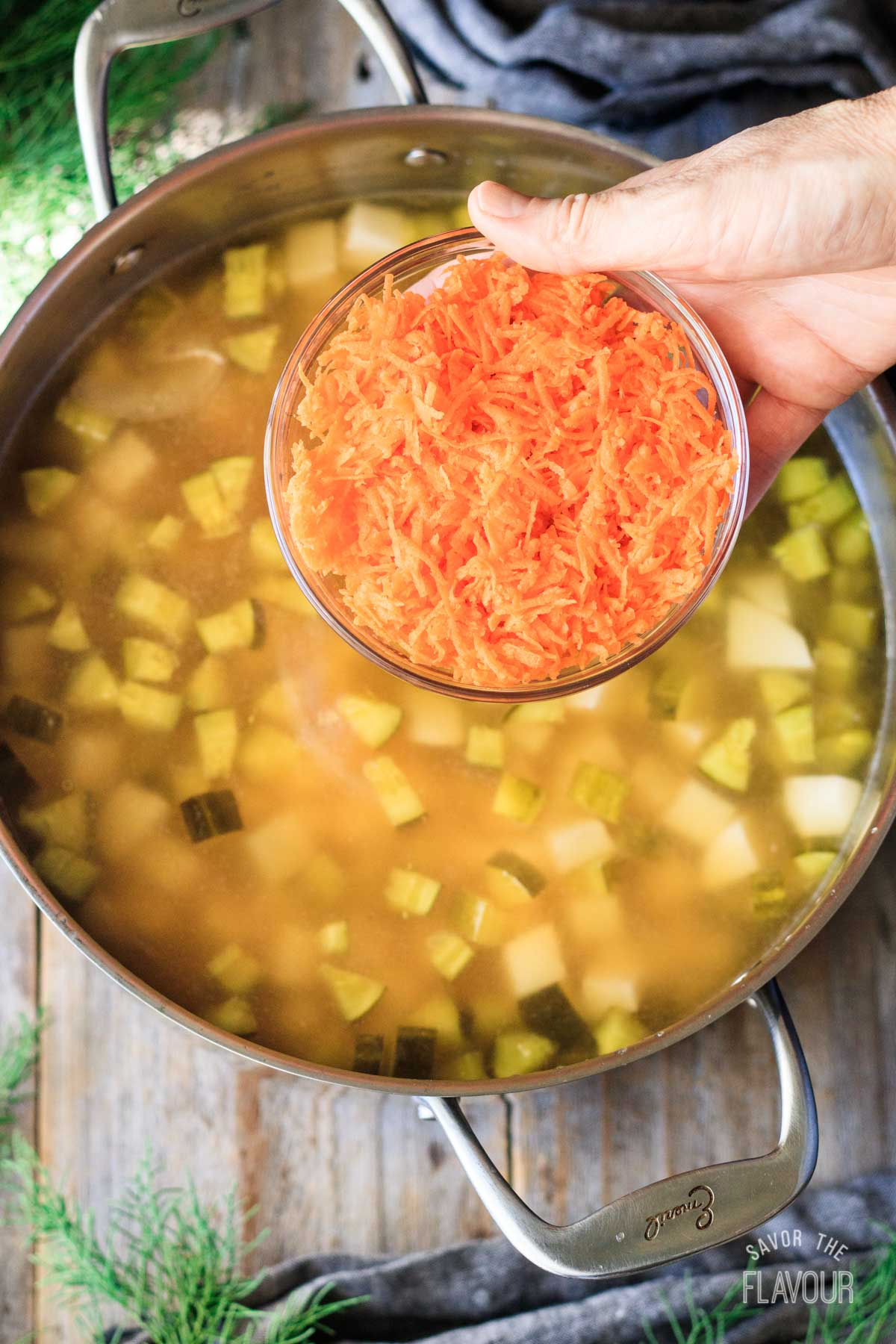 person holding a bowl of grated carrots above a pot of soup