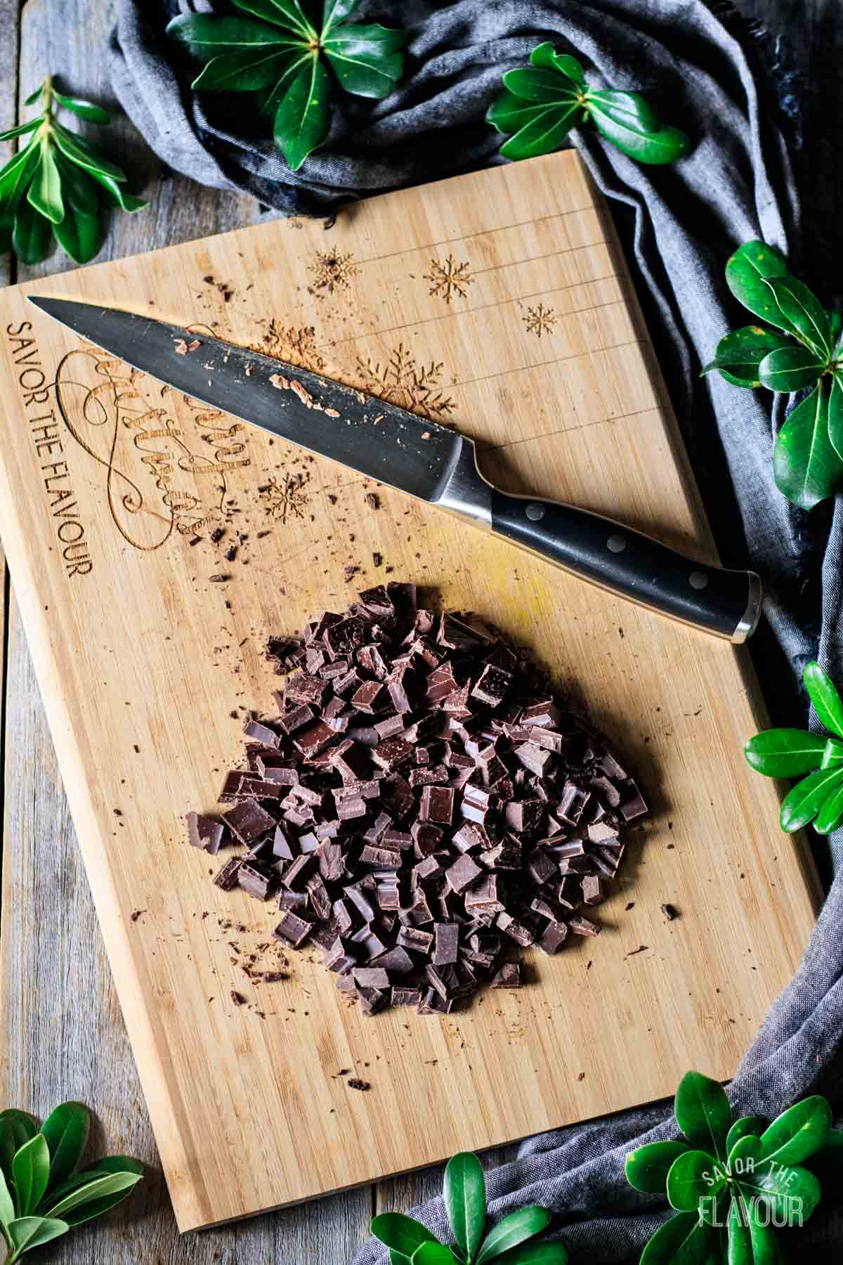 chopped dark chocolate on a cutting board with a knife