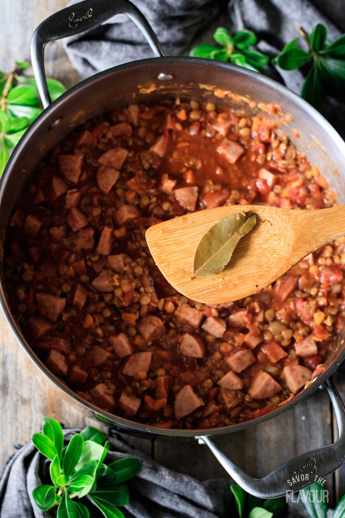 removing the bay leaf from the pot of lentil stew