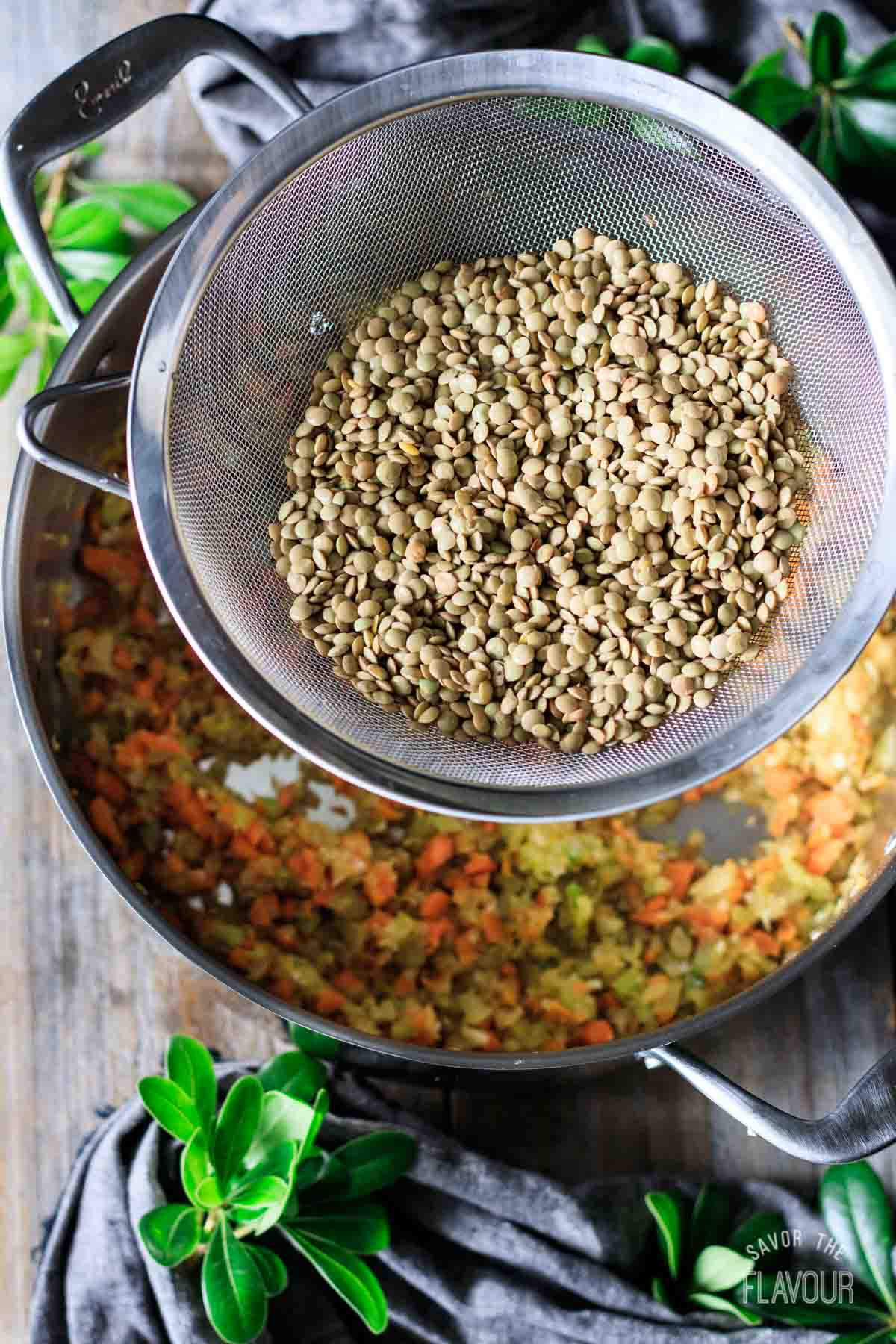 adding rinsed lentils to the pot of sauteed veggies