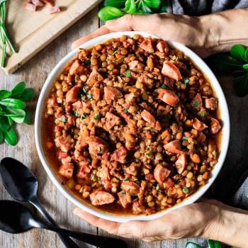 person holding a bowl of lentil stew with kielbasa sausage