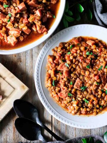 bowl of lentil stew with kielbasa sausage and two spoons