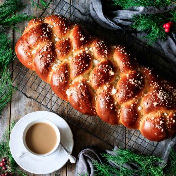 loaf of pulla bread on a cooling rack with a cup of coffee