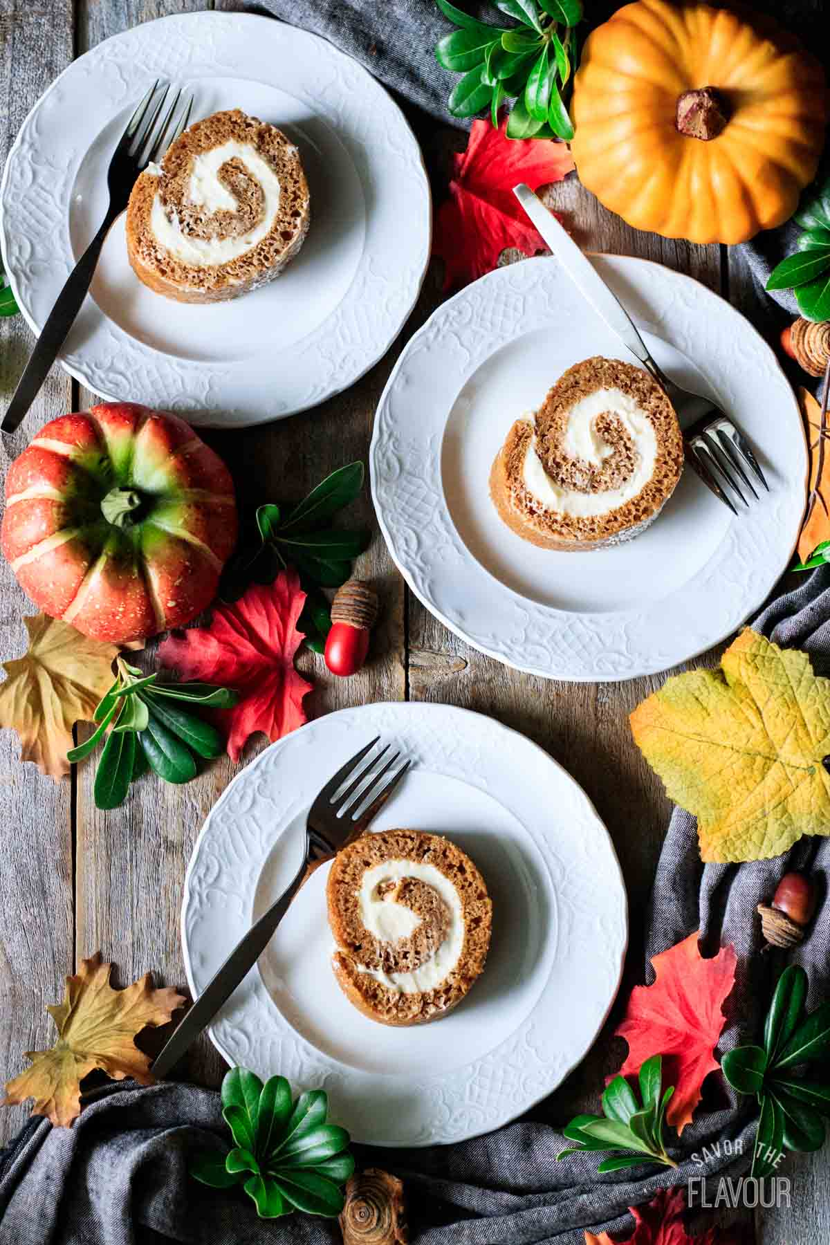 three slices of pumpkin roll on plates with forks