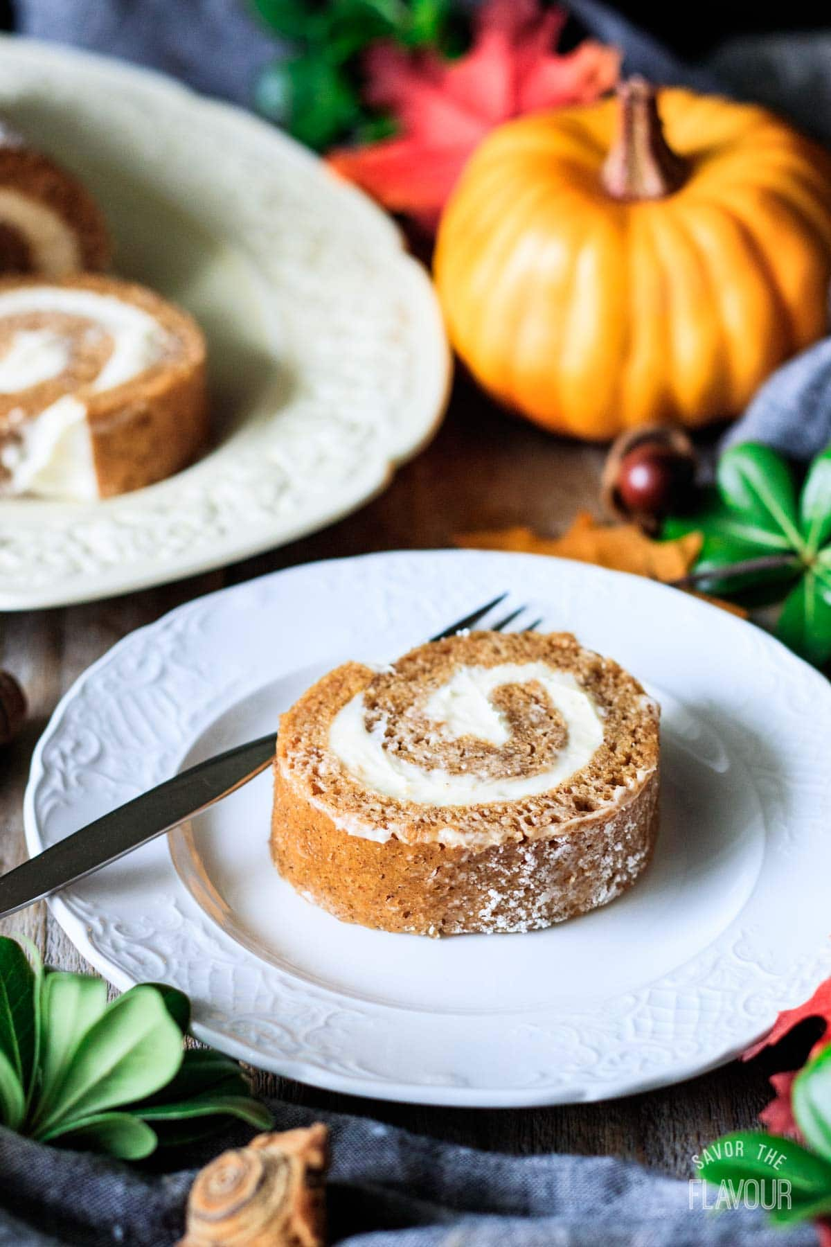 slice of pumpkin roll on a plate with a fork