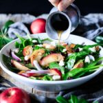 pouring dressing on a bowl of spinach apple salad