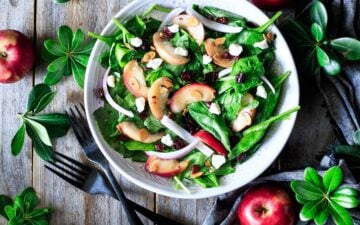 bowl of spinach apple salad with two forks