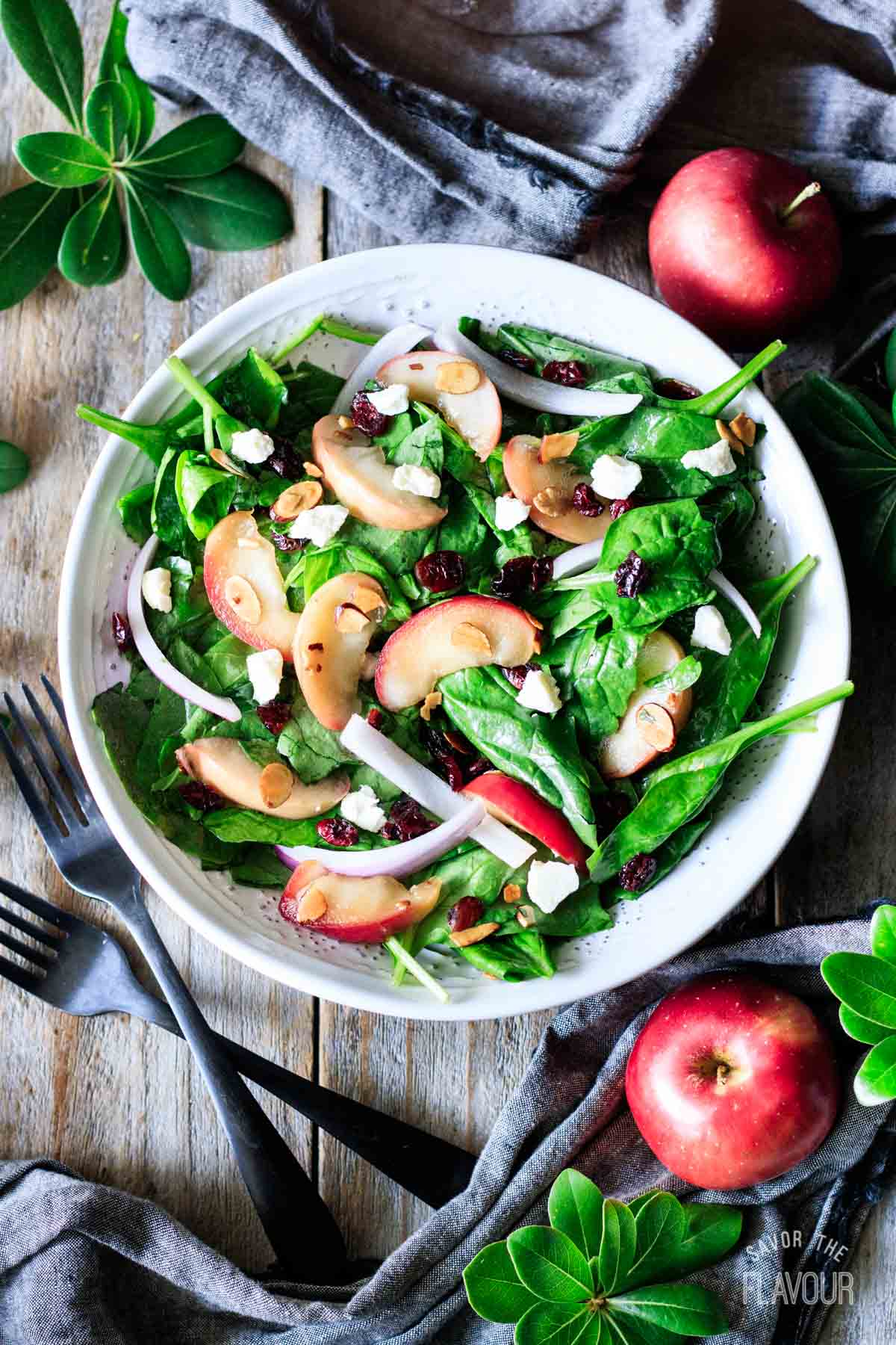bowl of spinach apple salad with two apples