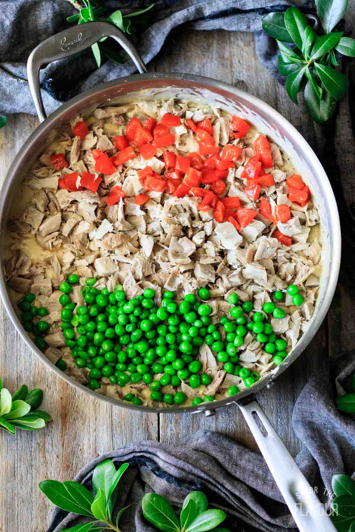 adding turkey, peppers, and peas to turkey a la king