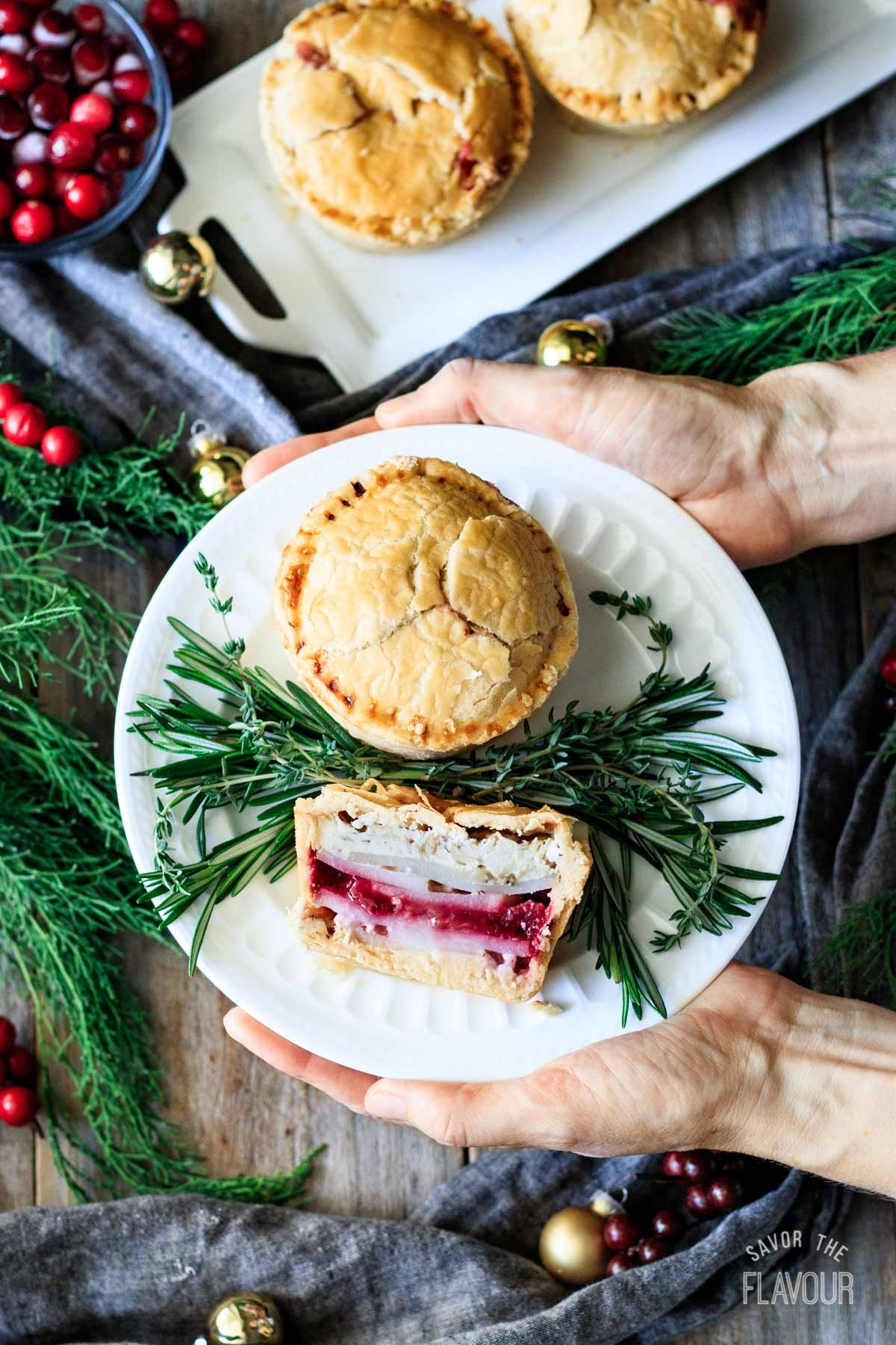 person holding a plate of turkey cranberry pies