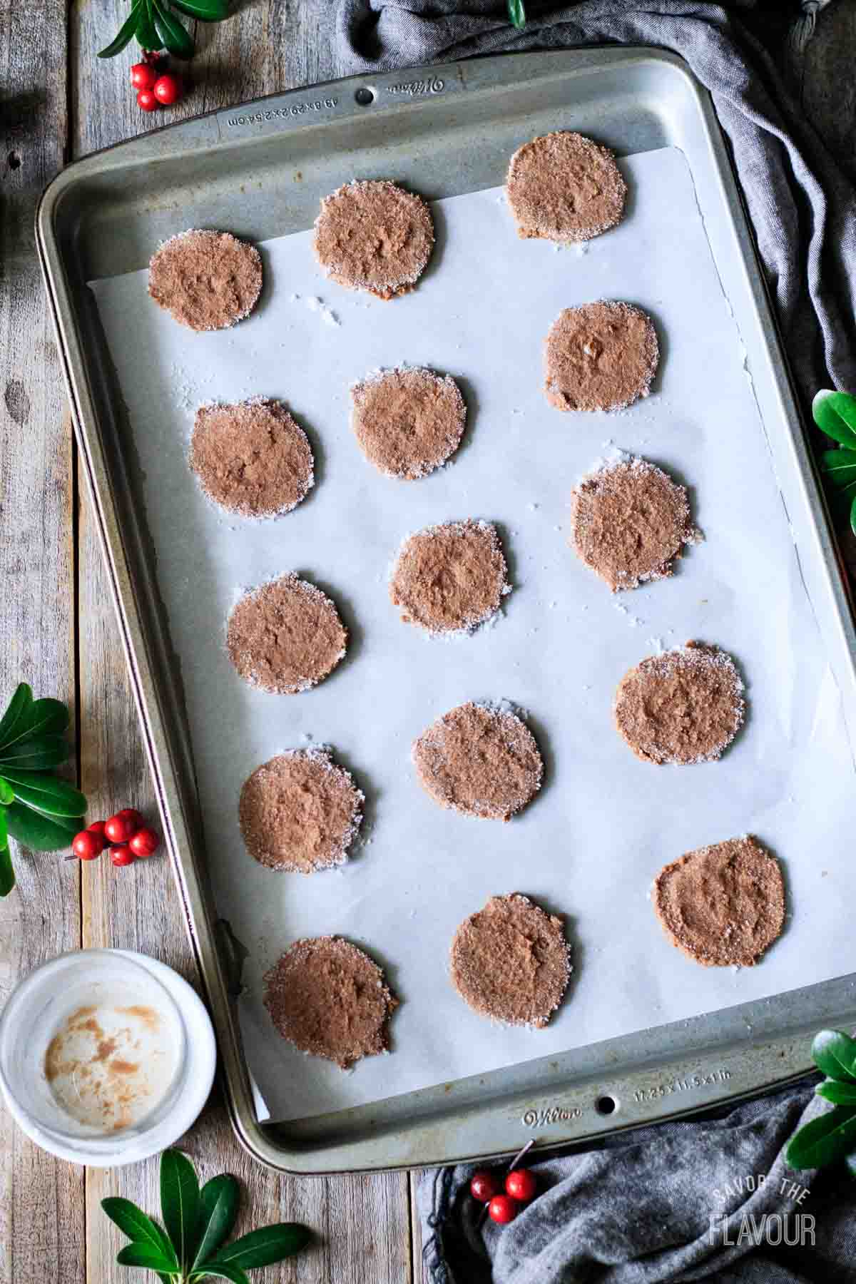 flattened chocolate cookie dough balls on a cookie sheet