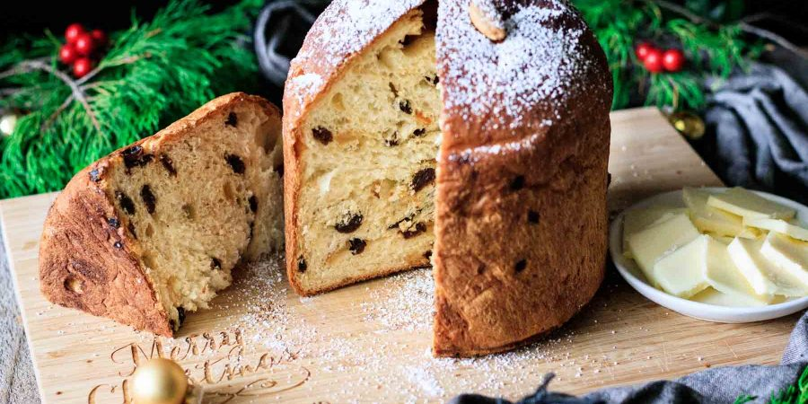 loaf of panettone and a butter dish on a cutting board