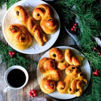 two plates of St. Lucia buns with a cup of coffee