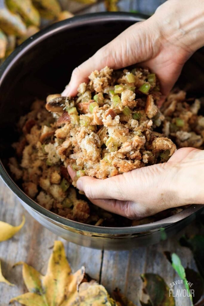 mixing the turkey stuffing ingredients in a bowl