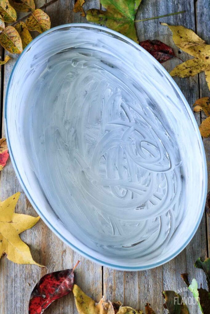 buttered oval glass casserole dish