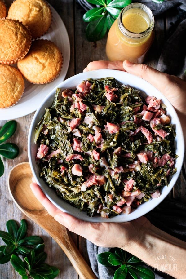 person holding a bowl of collard greens