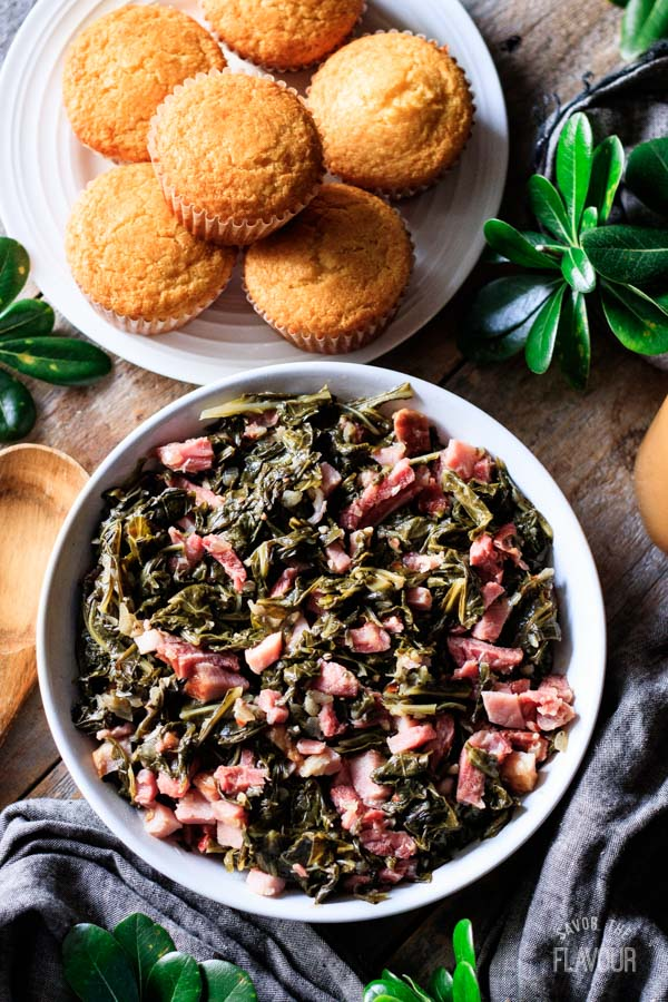 bowl of collard greens with cornbread muffins