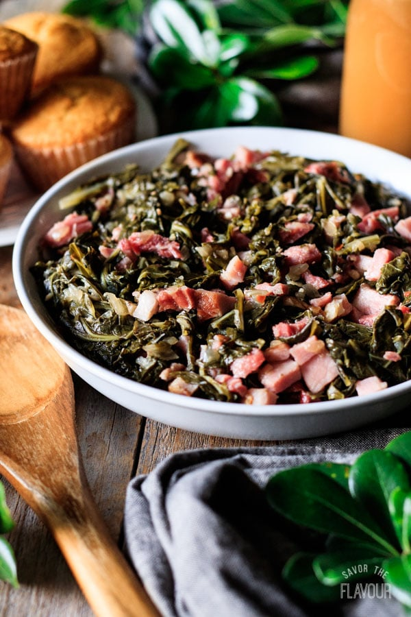 bowl of collard greens with a wooden spoon