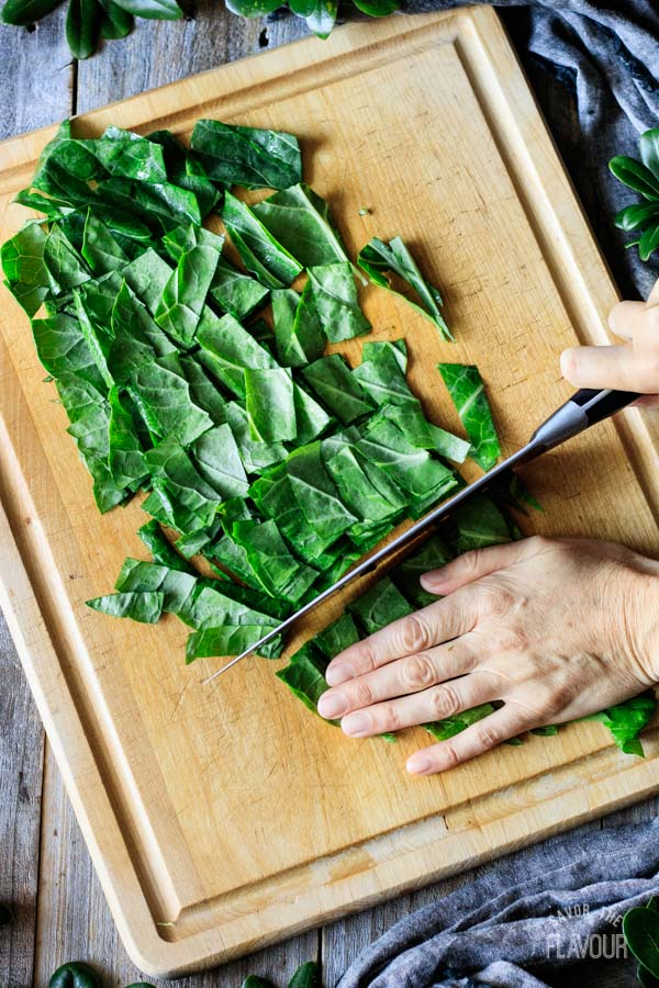 person cutting collard greens into smaller pieces