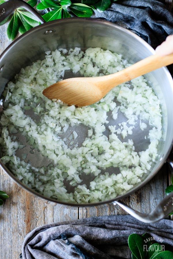 stirring chopped onions in a pot