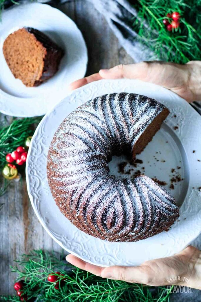 person holding a gingerbread bundt cake on a plate