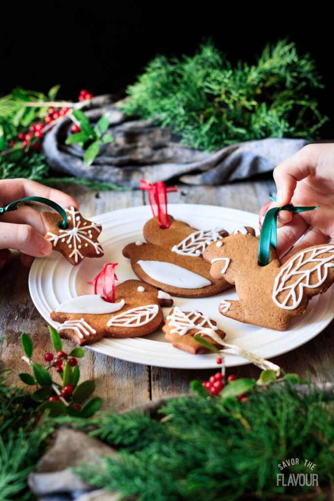 people picking up gingerbread cookies from a plate